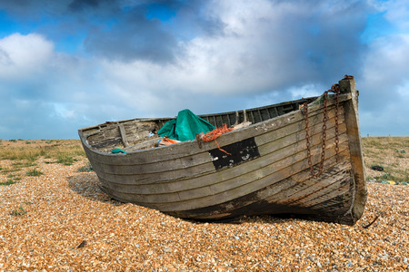 shingle: An old weathered wooden fishing boat under a blue sky on a shingle beach Stock Photo