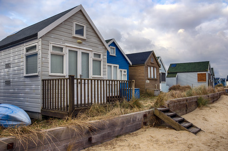 hengistbury: Beach huts under a cloudy sky on Mudeford Spit at Hengistbury Head near Christchurch in Dorset Editorial