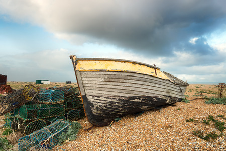 lobster boat: An old wooden fishing boat rests on a shingle beach alongside abandoned lobster pots