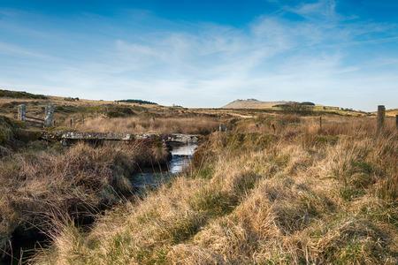 bodmin: A small stone clapper bridge over De Lank River on Bodmin moor in Cornwall as it winds it