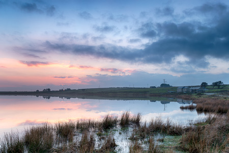 bodmin: Dramatic dusk at Dozmary Pool an historic landmark steeped in Arthurian legend on Bodmin Moor in Cornwall