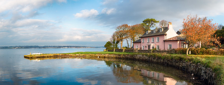 Pink cottage on the South West Coast path as it passes through Empacombe Quay at Mount Edgcumbe in Cornwall