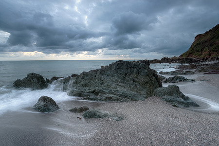 grey skies: Grey cloudy skies over the beach at Portwrinkle on the Cornish coastline