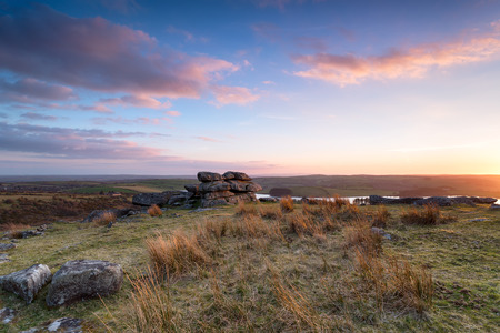 bodmin: Beautiful sunset over granite rock formations at Tregarrick Tor overlooking Siblyback lake on Bodmin Moor in Cornwall