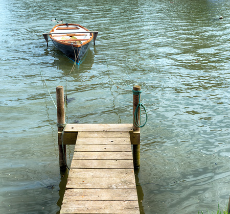 A samll rowing boat moored to a wooden jetty on the banks of the Tresillian river in Cornwall