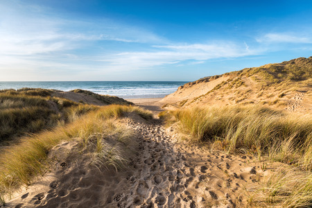 A path leading through sand dunes at Holywell Bay, a large sandy beach backed by dunes near Newquay on the north coast of Cornwall Stock Photo