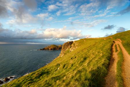 south west coast path: Cielo drammatico sulla South West Coast Path a Pentire testa con il groppe in lontananza