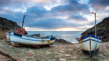 south west coast path: Fishing boats on the South West coast path as it passes through Penberth Cove near Lands End in Cornwall Stock Photo