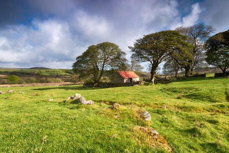 mire: An old stone barn with a red roof at Emsworthy Mire on Dartmoor National Park in Devon