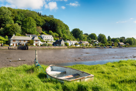 rowing boat: An old rowing boat moored to a grassy bank on the river Lerryn in Cornwall Stock Photo