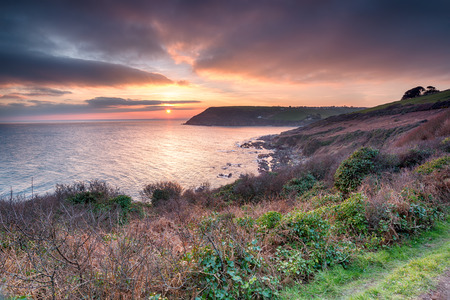 south west coast path: Stunning sunset from the South West Coast Path at Talland Bay on the south coast of Cornwall Stock Photo