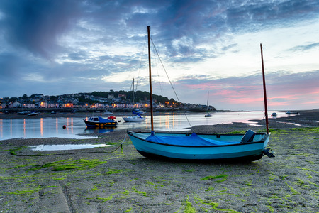Sunset over a blue boat on the beach at Instow, looking out at the pretty fishing village of Appledore just outside of Bideford on the Devon coast Stock fotó