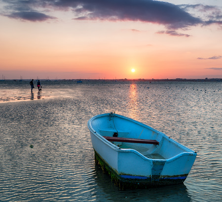 A small blue boat on the beach at Sandbanks in Poole, Dorset