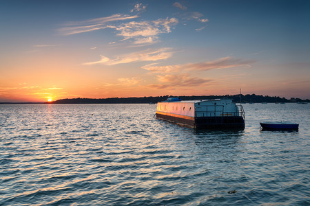 �ber Wasser: House boat at sunset afloat on Bramble Bush Bay at Studland on the dorset coast, looking out to Brownsea Island Lizenzfreie Bilder