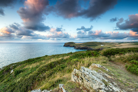 quin: Lundy Bay on the north coast of Cornwall from Trevan Point, looking out to Doyden Castle and cottages at Port Quin in the far distance
