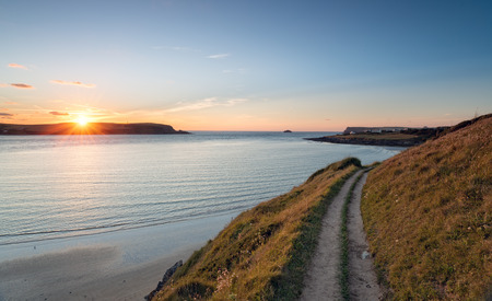 south west coast path: Sunset from the South West Coast Path as it approaches Daymer Bay near Padstow in Cornwall Stock Photo