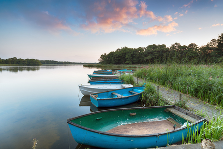Boats moored to an old wooden jetty at Filby Broad on the Norfolk Broads near Great Yarmouth