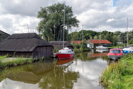 thatched: Boats and thatched boat houses on Hickling Broad in Norfolk