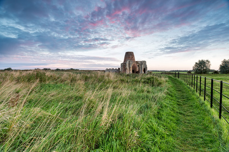 gatehouse: Sunrise at St Benets Abbey on the Norfolk Broads, all that remains are the ruins of the gatehouse and windmill Stock Photo