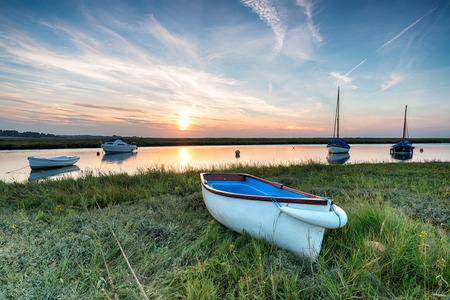 salt marsh: Sunset over boats on the salt marshes at Blakeney on the north coast of Norfolk Stock Photo