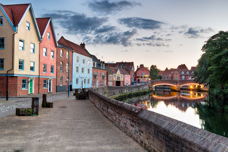 Colorful houses at dusk on the river Yare as it flows through the city of Norisch in Norfolk