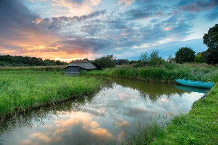 boat house: Stunning sunset over a boat and thatched boat house in reeds on the Norfolk Broads Stock Photo