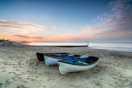 pesca: Impresionante la salida del sol sobre una fila de barcos de pesca en la playa de Bournemouth, en Dorset, con el muelle en la distancia