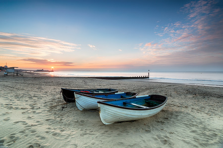 bournemouth: Stunning sunrise over a row of fishing boats on Bournemouth beach in Dorset, with the pier in the far distance