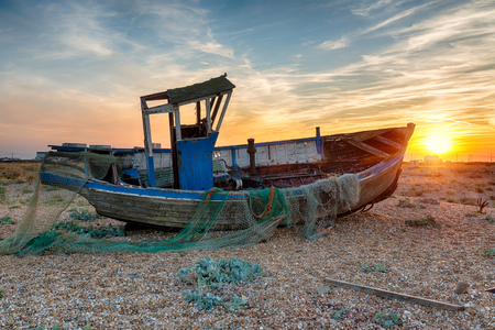 dungeness: Stunning sunset over an old wooden fishing boat on the beach at Dungeness on the Kent coast Stock Photo