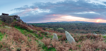 craggy: A panoramic view of an Autumn sunset over Helman Tor a steep craggy outcrop of granite along the Saints Way long distance path in Cornwall Stock Photo