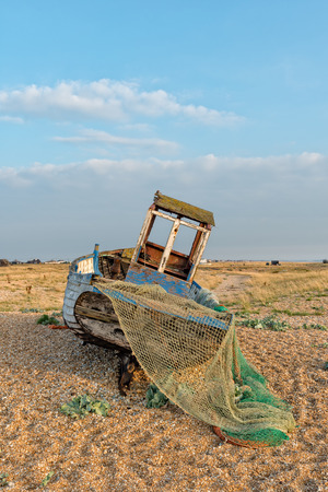 shingle beach: An old wooden fishing boat on a shingle beach at Dungeness on the Kent coast