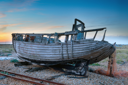dungeness: Beautiful sunset over an old fishing boat at Dungeness in Kent Stock Photo