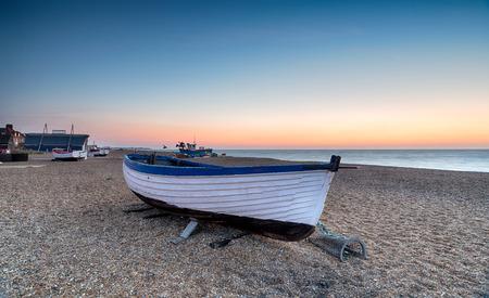 서퍽 해안의 Aldeburgh의 해변에서 낚시 보트 위로 일출