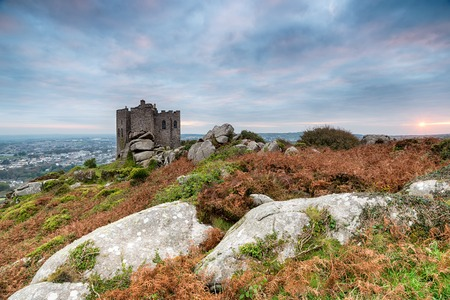 Cloudy sunrise over Carn Brea and its castle, a rugged tor topped hill above Redruth and Camborne in Cornwall Stock Photo