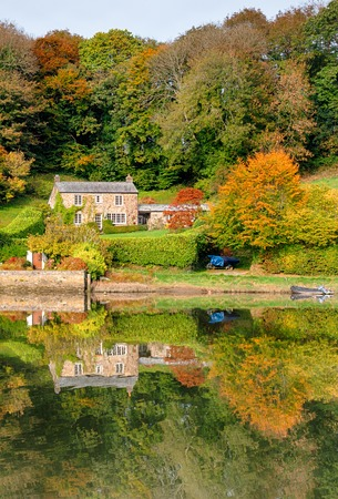 vibrant cottage: A beautiful cottage surrounded by Autumn colour and reflected in a lake