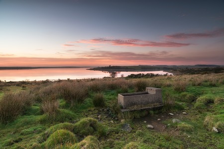 bodmin: A stone cattle trough at dusk in a field by a lake on Bodmin Moor in Cornwall Stock Photo