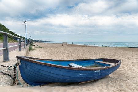 Een roeiboot op het strand van Bournemouth op de kust van Dorset Stockfoto