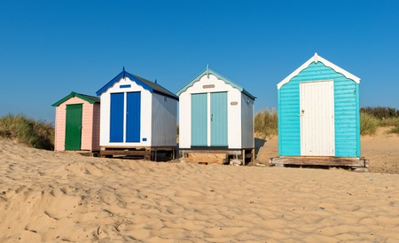 A row of clouful huts on a sandy beach backed by dunes at Southwold on the Suffolk coast