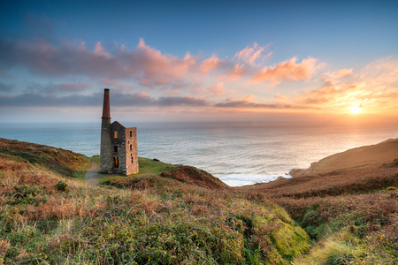 Stunning sunset on the South West Coast Path as it passes the ruins of the Wheal Prosper engine house on cliffs at Rinsey Head near Porthleven in Cornwall