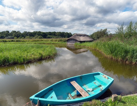boat house: A boat house and blue boat on Hickling Broad in Norfolk Stock Photo