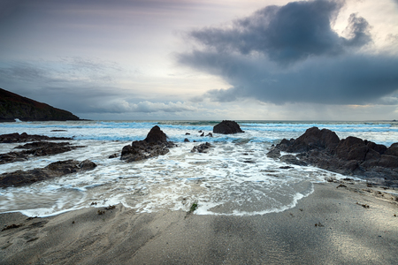 south coast: Storm clouds over Hemmick Beach on the south coast of Cornwall Stock Photo