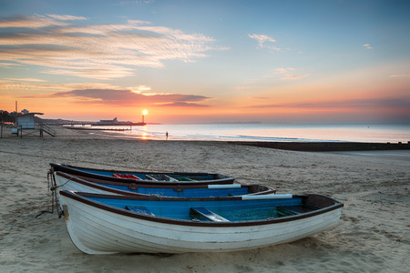 of the united kingdom: Stunning sunrise ove rfishing boats at Durley Chine on Bournemouth beach in Dorset with the sun rising over the end of the pier