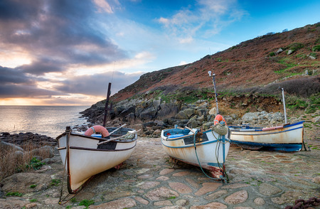 Dramatic sky at dawn over fishing boats at Penberth Cove in the far west of Cornwall Stock Photo