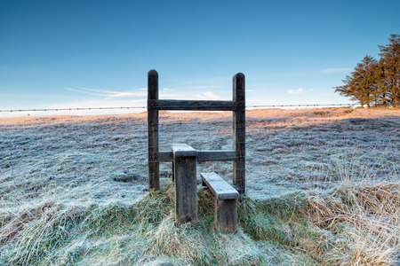 stile: A frosty stile over a barbed wire fence on a cold winter morning on Bodmin Moor in Cornwall