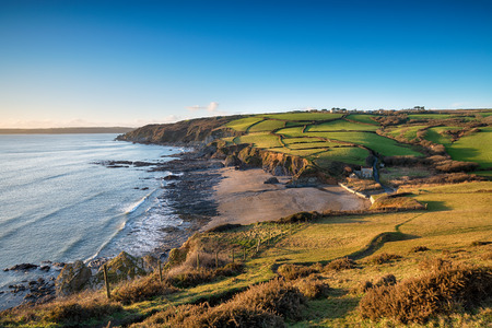 south west coast path: Walking the South West Coast Path as it descends from Dodman point to Hemmick Beach on the south coast of Cornwall