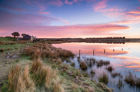 bodmin: A beautiful sunrise over cottages at Dozmary Pool a mysterious lake steeped in Arthurian legend near Bolventor on a remote part of Bodmin Moor in Cornwall