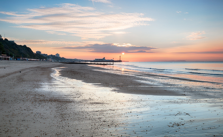 seashores: Sunrise over Bournemouth beach with the pier in the distance Stock Photo
