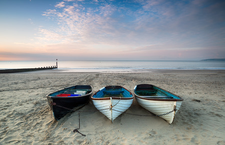 chine: Three wooden fishing boats on the beach at Durley Chine in Bournmouth, Dorset