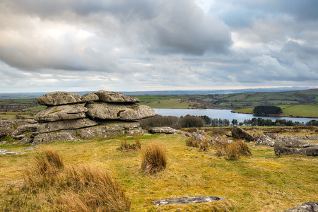 bodmin: Dramatic moody sky over rock formations on Tregarrick Tor on Bodmin Moor in Cornwall with Siblyback Lake in the distance