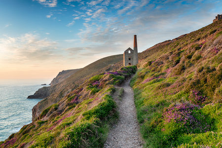 south west coast path: Hazy summer evening on the South West Coast Path as it approaches the ruins of the Wheal Coates mining engine house near St Agnes in Cornwall Stock Photo